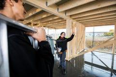 Scala di trasporto di Gesturing While Colleague del carpentiere alla costruzione Immagini Stock Libere da Diritti