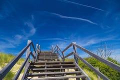 Scala e cielo blu di legno fra le dune e l'alta erba Immagine Stock