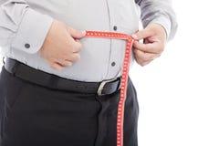 Scala grassa di uso dell'uomo di affari per misurare il suo giro vita Immagine Stock