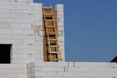 Scala marrone di legno dal muro di mattoni grigio di una casa non finita contro il cielo blu fotografia stock libera da diritti