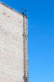 Scala metallica sul muro di mattoni bianco Priorità bassa del cielo Immagine Stock Libera da Diritti
