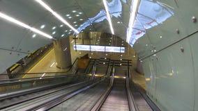 Scala mobile moderna che si abbassa, passeggeri di trasporto verso la stazione della metropolitana in sotterraneo stock footage