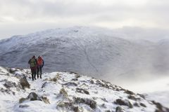 Scalando attraverso la neve ed il ghiaccio fotografia stock