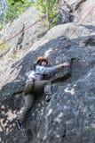 Scalata di pratica della giovane donna graziosa sulle rocce naturali che spendono così il suo svago attivo Immagini Stock