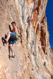 Scalatore all'alta parete rocciosa ripida con la pietra arancio di colore dell'ingranaggio Fotografia Stock