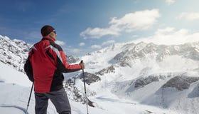 Scalatore che esamina un paesaggio nevoso della montagna in un giorno di inverno soleggiato Immagine Stock