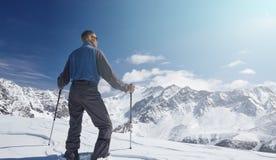 Scalatore che esamina un paesaggio nevoso della montagna in un giorno di inverno soleggiato Immagini Stock Libere da Diritti
