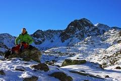 Scalatore che riposa su una roccia in montagne di Retezat, Romania Immagini Stock