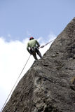 Scalatore che si arrampica su una roccia Fotografia Stock
