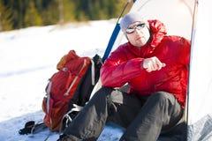 Scalatore con uno zaino vicino alla tenda Fotografia Stock
