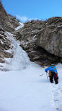 Scalatore del maschio icci che si avvicina ad una caduta di ghiaccio e ad un couloir nelle alpi svizzere Fotografia Stock