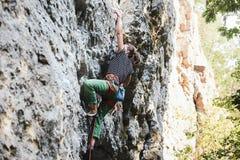 Scalatore della giovane donna che scala sulla scogliera Immagine Stock