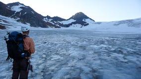 Scalatore di montagna che guarda fuori su un grande ghiacciaio nelle montagne di Silvretta in Svizzera fotografie stock