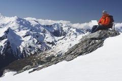 Scalatore di montagna che per mezzo del computer portatile sul picco di montagna Fotografie Stock Libere da Diritti