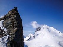 Scalatore di montagna che rappelling fuori da un ago tagliente della roccia su una cresta esposta della montagna sotto un cielo b fotografia stock