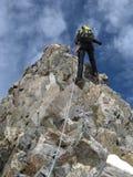 Scalatore di montagna che rappelling fuori da una cresta ripida e stretta della roccia che conduce giù da un alto picco nelle alp fotografia stock