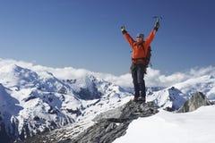 Scalatore di montagna con le armi alzate sul picco di Snowy Immagini Stock