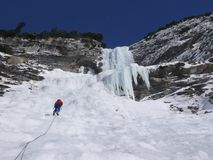 Scalatore di montagna maschio che rapelling fuori da una cascata congelata ripida e lunga nelle alpi svizzere nell'inverno profon Fotografia Stock
