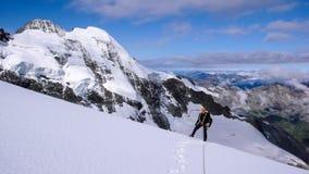 Scalatore di montagna maschio su un alto ghiacciaio alpino con una grande vista del paesaggio fantastico della montagna dietro lu immagine stock libera da diritti