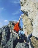 Scalatore di roccia che aderisce ad una scogliera Immagini Stock