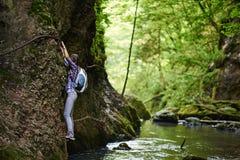 Scalatore di signora sui cavi di sicurezza sopra il fiume Fotografia Stock