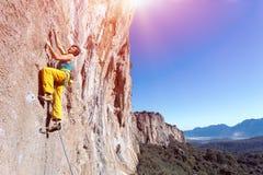 Scalatore estremo maschio maturo che si alza sulla parete rocciosa Immagine Stock