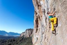 Scalatore estremo maschio maturo che si alza sulla parete rocciosa Fotografie Stock Libere da Diritti