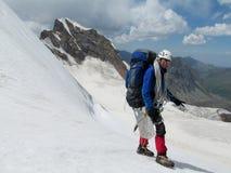 Scalatore felice sull'itinerario dell'alpinista della neve Fotografia Stock