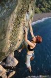 Scalatore femminile che scala senza corda su una parete rocciosa Fotografia Stock Libera da Diritti