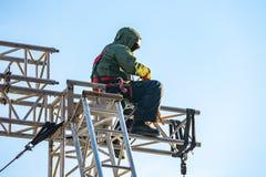 Scalatore industriale negli st di seduta dell'uniforme su una struttura edile Fotografie Stock