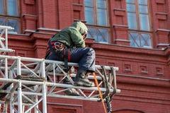 Scalatore industriale negli st di seduta dell'uniforme su una struttura edile Fotografia Stock