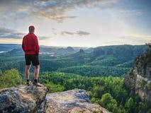 Scalatore o viandante di montagna di misura su una sommità rocciosa che guarda giù fotografie stock