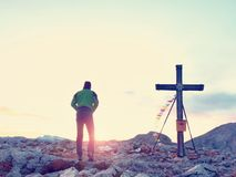 Scalatore solo dell'uomo vicino all'incrocio della sommità sul picco, alpi della dolomia, Austria Sera ventosa soleggiata Immagini Stock Libere da Diritti