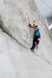 Scalatore su ghiaccio con il climbe delle piccozze da ghiaccio la parete Immagini Stock Libere da Diritti