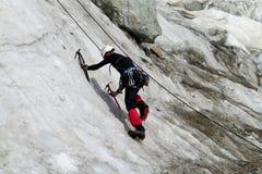 Scalatore su ghiaccio con il climbe delle piccozze da ghiaccio la parete Fotografie Stock