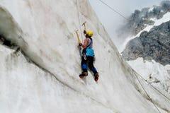 Scalatore su ghiaccio con la scalata verticale delle piccozze da ghiaccio Immagine Stock