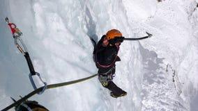 Scalatore su ghiaccio maschio su una cascata congelata ripida un bello giorno di inverno nelle alpi svizzere Immagini Stock Libere da Diritti