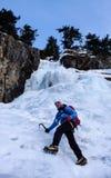 Scalatore su ghiaccio maschio in una giacca blu su una cascata congelata splendida che scala nelle alpi nell'inverno profondo Immagine Stock
