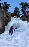Scalatore su ghiaccio maschio in una giacca blu su una cascata congelata splendida che scala nelle alpi nell'inverno profondo Immagini Stock Libere da Diritti