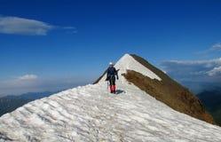 Scalatore sull'itinerario dell'alpinista della neve Immagini Stock
