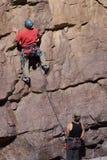 Scalatore sulla parete con belayer Fotografie Stock