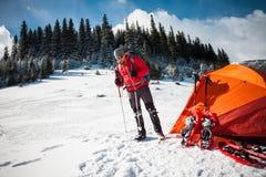 Scalatore vicino alla tenda con le racchette da neve Immagine Stock