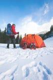 Scalatore vicino alla tenda con le racchette da neve Fotografia Stock