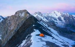 Scalatori arancio soli della tenda negli alti moutains Immagini Stock