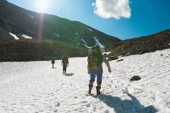 Scalatori che camminano in cima alla montagna su neve Immagini Stock