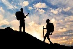 Scalatori della siluetta che salgono la montagna Fotografia Stock
