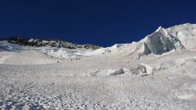 Scalatori di montagna su un ghiacciaio ripido sul loro modo ad un'alta sommità alpina presto nel mornin Immagine Stock