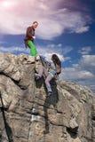 Scalatori femminili che si aiutano sulla parete della roccia Fotografia Stock Libera da Diritti