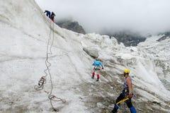 Scalatori su ghiaccio con il climbe delle piccozze da ghiaccio la parete Fotografia Stock Libera da Diritti