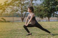 Scaldarsi atletico dell'asiatico della donna e giovane seduta dell'atleta femminile Fotografie Stock